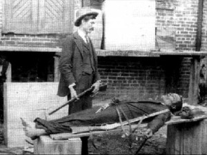 Railroad Bill's body on display. His killer, Constable J.L. McGowan, stands over him.