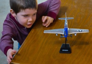 Son #4 admires his completed model airplane in Hangar One